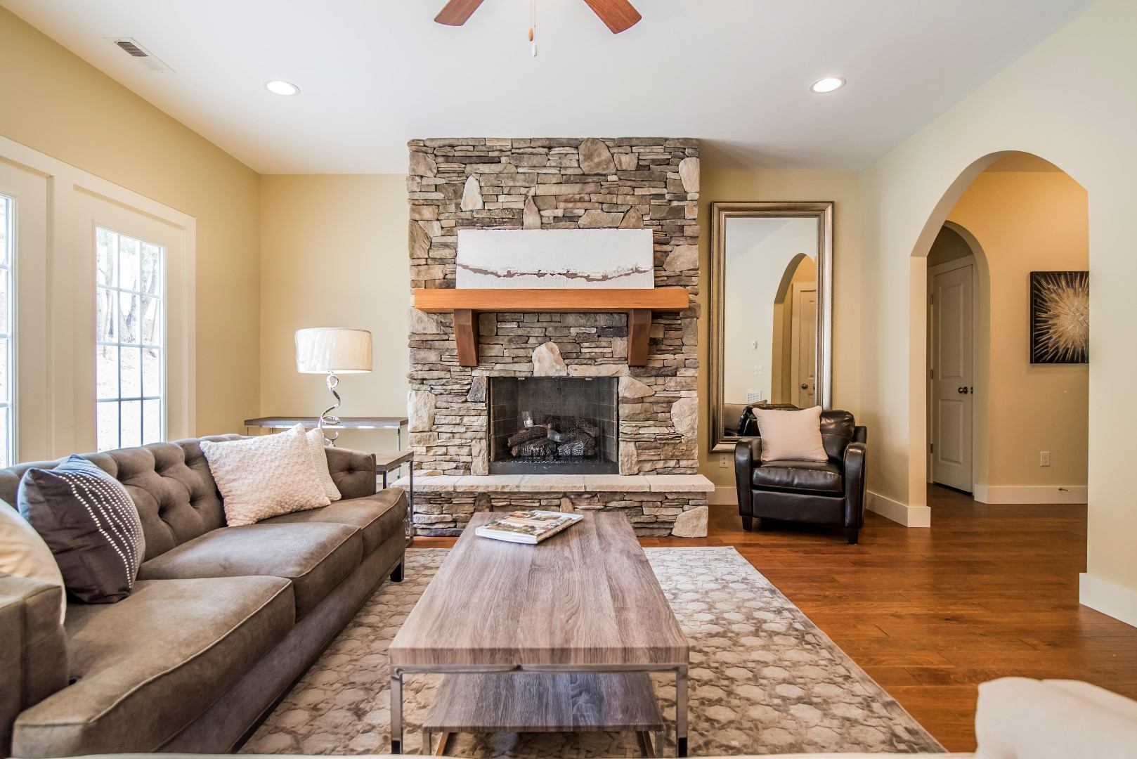 Living room with coffee table, hardwood floors, and stone fireplace.